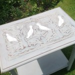 Hand-painted table with carved dove top